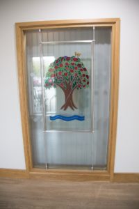 Arthur Rank Hospice Charity proudly displays the Royal stained glass window, previously housed at the Mill Road site, in the Evelyn Day Therapy Window at Shelford Bottom, Cambridge