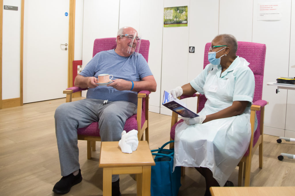 Patient wearing a perspex visor in day therapy enjoys a cup of tea, as he chats to a nurse wearing a face mask