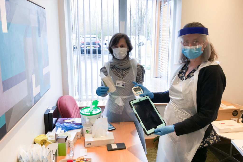 Two volunteers each in PPE displaying tablets, testing and cleaning kits