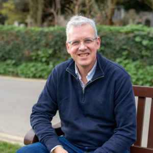 Andrew Kellard smiling, sat on a wooden bench with greenery behind him