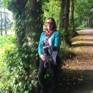 Sally Milligan at the front of a sunlit avenue of trees