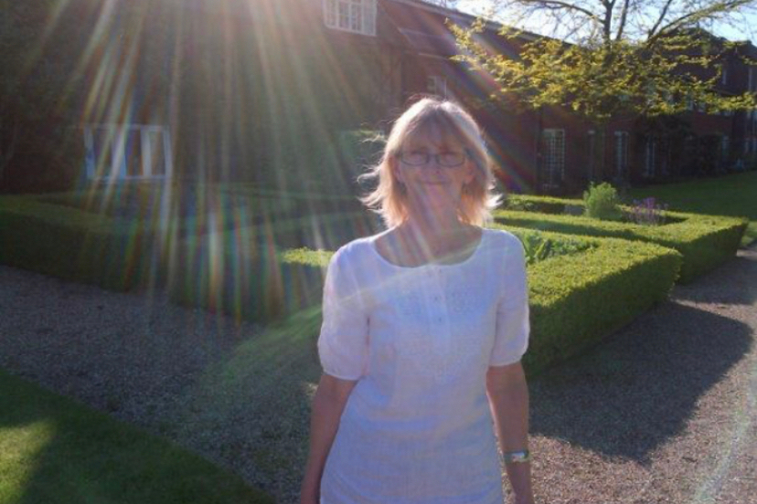 Linda with rays of sun behind her head, in a white dress enjoying a day at Champneys with Natalie in 2016