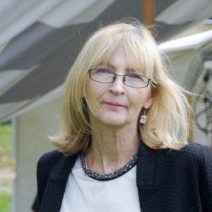 Informal portrait shot of Linda in a suit jacket, with her shoulder length blonde hair being blown behind her left shoulder