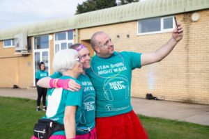 3 Star Shine Night Walkers dressed in green t-shirts smiling as they take a selfie