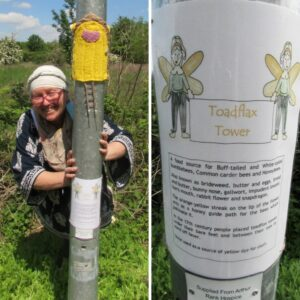 Lady with glasses and a white hat smiling near the lampost and yellow knitted door on the lamp post leading to Arthur Rank Hospice