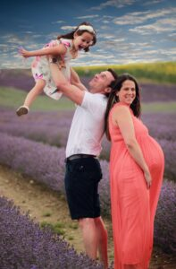 Lee holding his daughter in the air with his pregnant wife standing next to him with a lavender field behind them