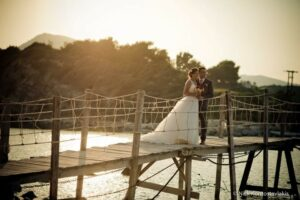 Lee and his wife in her Wedding Dress on a bridge in the sunset