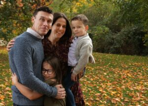Lee with his wife and their 2 children hugging in near the Autumn leaves