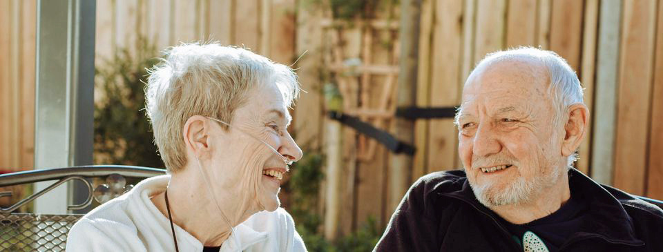 Laine and Geoff laughing together in the gardens at the Hospice