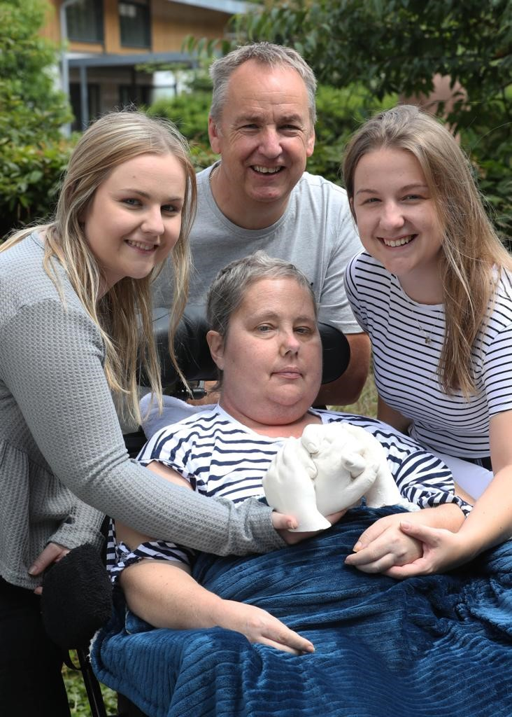 Family in Hospice garden with their mum, holding their hand cast