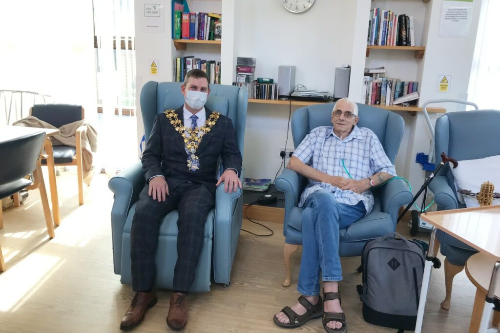 The Mayor of Wisbech sittingon a chair with a male patient sitting on a chair next to him