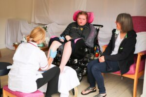 A young lady in a wheelchair enjoys a foot massage from one of the teams' complementary therapists, in Arthur's Shed