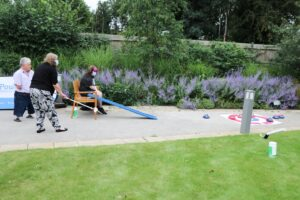 Young lady has a go at seated curling as family members and hospice colleagues cheer her on