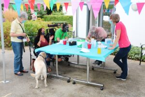 The arts and crafts table with a young man painting a cap, a PAT dog and staff, with colourful bunting in the foreground