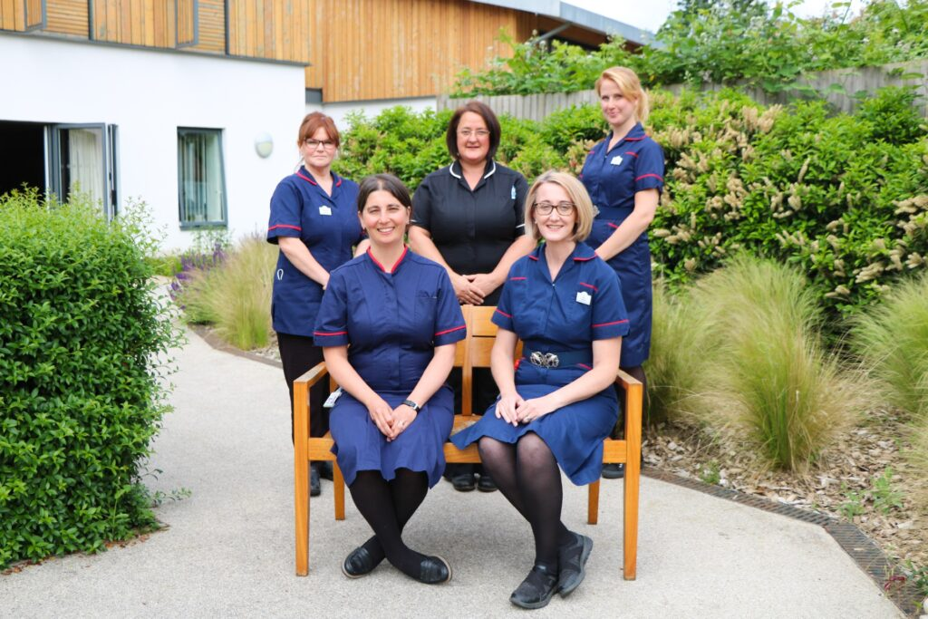 Five members of the Palliative Care Hub Team, who are Clinical Nurse Specialists in their navy uniforms, at a bench in the Hospice's gardens